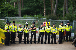 © London News Pictures. 17/08/2013. Balcombe, UK. POlice guard the entrance to the Cuadrilla drilling site in Balcombe, West Sussex which has been earmarked for fracking. Cuadrilla has temporarily ceased drilling at the site under advice from the police after campaign group No Dash For Gas threatened a weekend of civil disobedience. Photo credit: Ben Cawthra/LNP