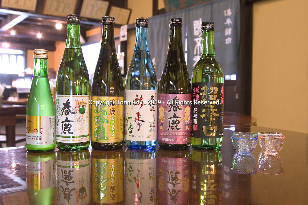"This is the Harushika Brewery, a sake maker in the ancient city of Nara, Japan Seen here are varieties that are offered in their tasting room. They are (L to R): ..- Tokimeki, a sparkling pure rice sake.- Shiboribana, a namazake or unpasteurized sake.- Daiginjo, a premium pure rice sake.- Arabashishiri Ichiban, a nama-genshu or unpasteurized genshu sake..- The 1300th Aniversary of Nara Heijo-kyo's Capitol, a commemorative ginjo sake.- Karakuchi, a very dry junmaishu pure rice sake..Founded in Nara in 1884 (the city thought to be the birthplace of sake), this sake maker which prides itself on making high quality sake manufactures a variety of sake with it's signature brews being ""light, mellow tasting sake with a flowery yet sharp flavor, using highly polished rice in the old Nara tradition of Nanto Morohaku brewing methods"". The name Harushika which literally means ""spring deer"" utilizes two kanji characters; one used in the name of Nara's historic Kasuga shrine, and the other for deer, which were considered gods in older times. Today Harushika sake has an excellent reputation in Japan and is exported to 10 countries around the world including France and the USA where their biggest international sales are. The New York area in particular is a big market for Harushika. The Harushika Brewery is located in the historic Naramachi quarter of Nara where they have a tasting room where visitors can sample various labels including a 400 yen ($4.50) set that includes five different kinds of Harushika. Well worth a visit when visiting Nara. Photo taken Dec. 18, 2009."