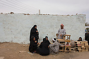 Locals talk in a quiet place at the weekly market at Qurna, a village on the West Bank of Luxor, Egypt.