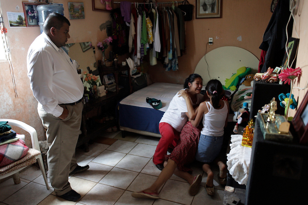 """Manteca"", _lard in English_  watches the reaction of three women after he notified them of the murder of a relative, Guatemala City,  Monday, June 23, 2009. Manteca, a funeral service salesman, went to the slum where the man was murdered to collect address and other information on the relatives in hopes of selling them a wake-coffin-burial package."