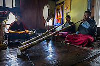 PARO, BHUTAN - CIRCA OCTOBER 2014: Bhutanese men chanting and playing Tibetan trumpets during a ritual in Paro, Bhutan