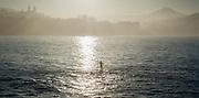 Man paddleboarding in La Concha beach in San Sebastian (Spain)
