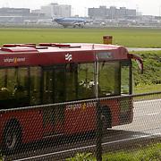 Vliegtuig landend op Schiphol, bus in de voorgrond, toerisme, openbaar vervoer,