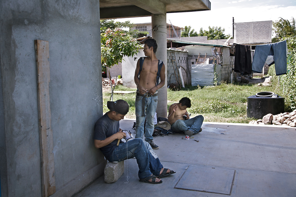 A group of friends who emigrated from El Salvador recently arrived, spend the day repairing their shoes carefully. Ixtepec-Oxaca-Mexico,2011