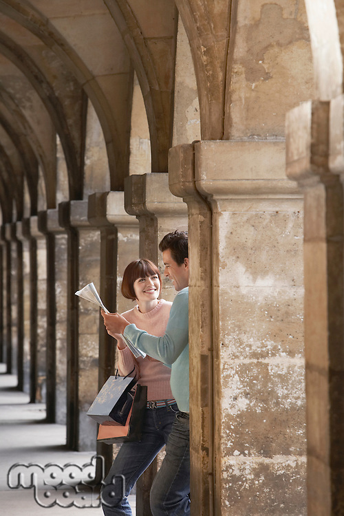 Couple with shopping bags looking at map under archway