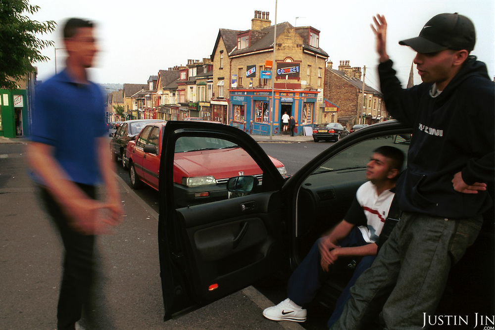 British-Pakistanis  hang out in Bradford, scene of heavy rioting by Asians in the summer of 2001...A generation of Muslims is growing up separated from the indigenous society. They go to predominantly Asian schools and hang out with Asian friends. Often the only contact between the two communities is through uncertain glances on the street or in local tabloids. Stuck in a Western society but feeling unwelcome and without many chances to escape from the ghetto, many youngsters seek identity in Islam...Photo by Justin Jin. Northern England, August 2001.