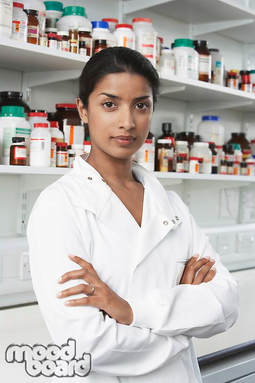 Female lab worker standing pill bottles behind