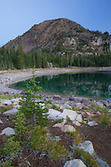 The still waters of Crater Lake reflect the surrounding hillsides, Eagle Cap Wilderness, Oregon