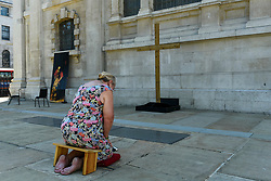© Licensed to London News Pictures. 25/06/2020. LONDON, UK.  Carol, a congregation member, kneels in the new outdoor Prayer Garden in the courtyard of St Martin-in-the-Fields, Trafalgar Square, where all are welcome to meditate, pray and discover peace and stillness at the heart of London.  The UK government has relaxed coronavirus pandemic lockdown restrictions allowing churches and other places of worship to open for private prayer from 15 June and, in the latest change, collective worship and communal prayer will be allowed from 4 July.  Currently, many churches are offering online services to their congregations. Photo credit: Stephen Chung/LNP