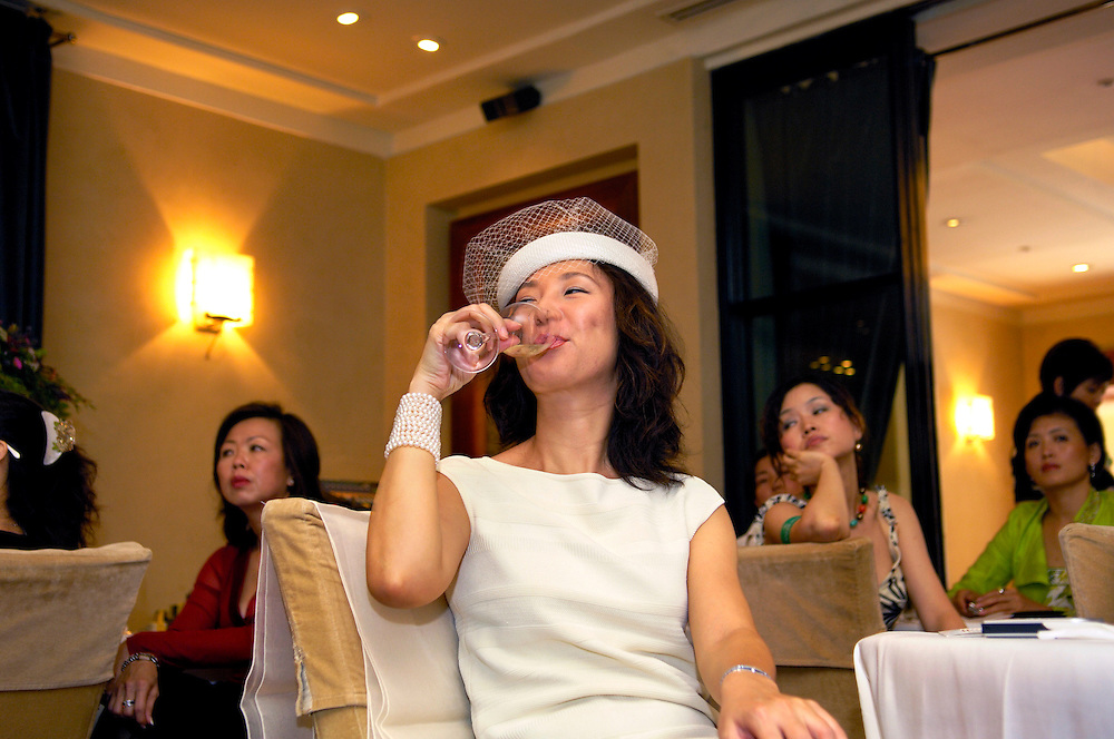 Wealth - distinctively dressed guest drinking prosecco at the exclusive prelaunch of a luxury Western cosmetics brand, at a five star hotel...From China [sur]real © Mark Henley..