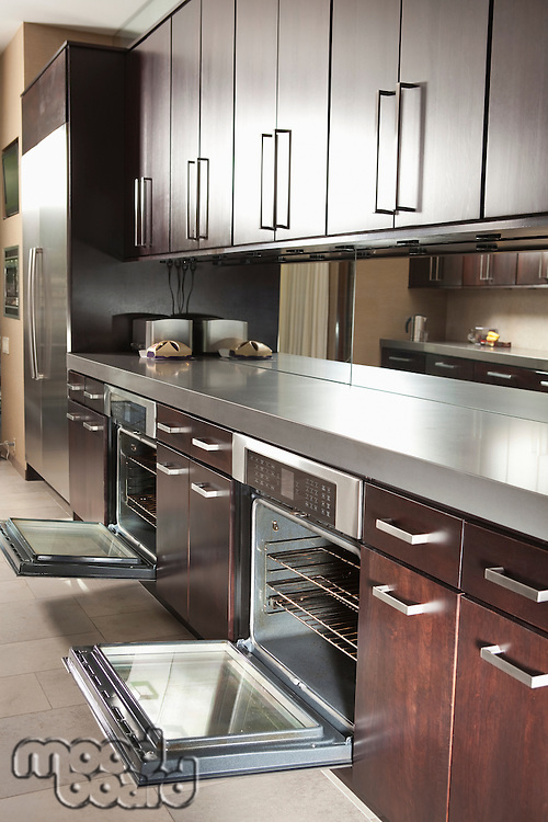 Dark wood kitchen with open oven doors
