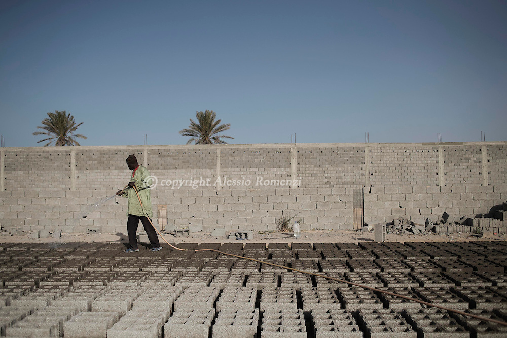 Libya, Misurata: A Nigerian worker is seen as he works in a concrete blocks factory in Misurata, on May 15, 2015. <br /> Migrants very often do menial jobs to gather enough money and pay smugglers who organise the boats for the Italian coasts. Alessio Romenzi