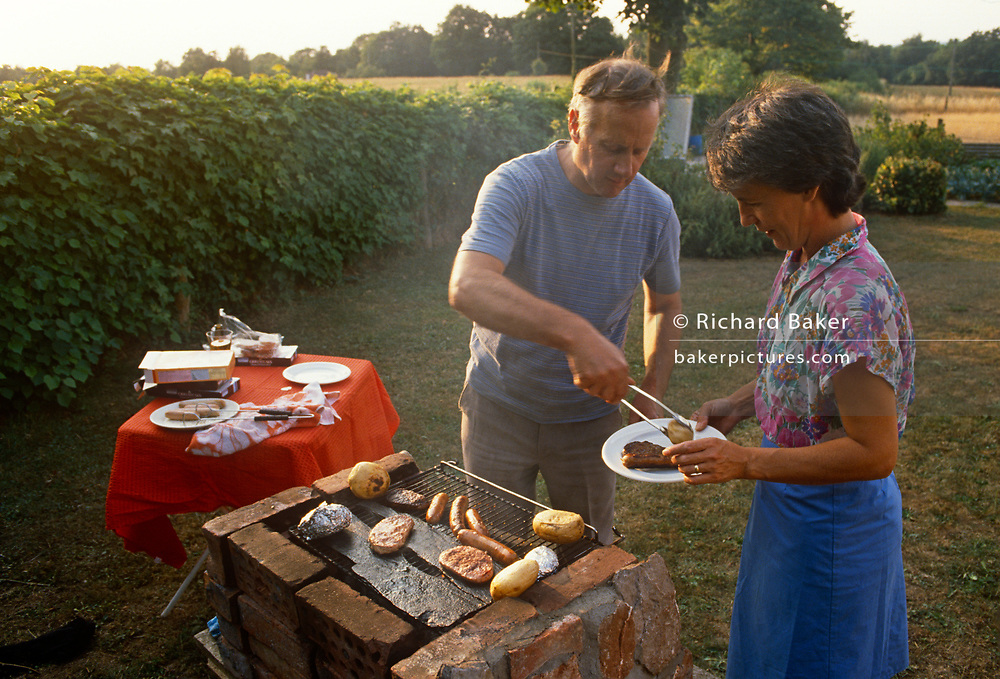 A middle-aged husband serves a plate of meat to his wife from the family home-made BBQ in the back garden on a summer's afternoon, in June 1989, in Wrington, North Somerset, England.