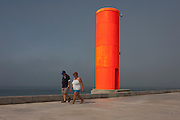 A couple walk past the fluorescent shipping navigation marker on Paredao da Praia da Barra, Costa Nova, Aveiro, Portugal.