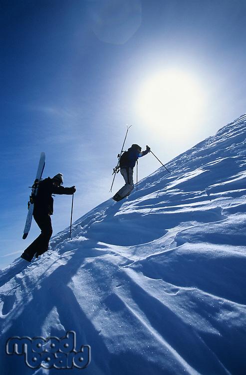 Skiers hiking to mountain summit