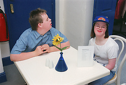 Teenage boy and girl with Downs Syndrome sitting at table in cafe waiting to place order,