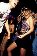 A blond woman with short skirt dances at a club, London, U.K.