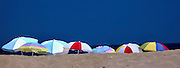 Beach umbrellas lined up on a summer beach day in Kitty Hawk North Carolina.