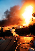 Propane tanks explode around Rob Brennan as he waters the roof of his mobile home during the Laguna Beach, Calif., fires. More than 300 homes were destroyed by the wind-fueled blaze set by an arsonist. Brennan's home went undamaged.