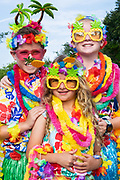 Children wearing Hawaiian themed costumes pose during the annual Independence Day parade July 4, 2019 in Sullivan's Island, South Carolina. The tiny Sea Island beach community across from Charleston, was once a quarantine station for enslaved Africans, and is now one of the most affluent, least diverse communities with one of highest per capita real estate costs in the United States.