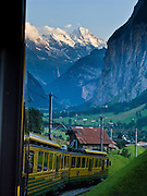 "At sunset, see Lauterbrunnen Breithorn (3780 meters or 12,402 feet elevation) from Wengernalpbahn cog train in Lauterbrunnen Valley, Berner Oberland, Switzerland, the Alps, Europe. The world's longest continuous rack and pinion railway (Wengernalpbahn) goes from Grindelwald up to Kleine Scheidegg and down to Wengen and Lauterbrunnen. The Bernese Highlands are the upper part of Bern Canton. IUNESCO lists ""Swiss Alps Jungfrau-Aletsch"" as a World Heritage Area (2001, 2007)."