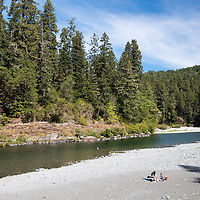 People sitting on the rocky riverbed at Jebediah Smith Redwoods State Park in Northern California, USA.