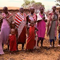 Africa, Kenya, Maasai Mara. Maasai mothers and children greet visitors to their boma at Olanana in the Maasai Mara.