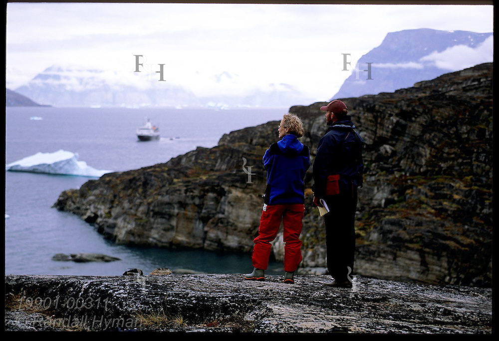 Man and woman stand on granite ledge overlooking fjord and cruise ship near Uummannaq Island; Qilakitsoq, Greenland.