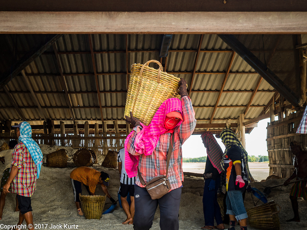 22 FEBRUARY 2017 - BAN LAEM, PETCHABURI, THAILAND: A salt worker carries a basket of salt to a waiting truck during the salt harvest in Petchaburi province of Thailand, about two hours south of Bangkok on the Gulf of Siam. Salt is collected in coastal flats that are flooded with sea water. The water evaporates and leaves the salt in large pans. Coastal provinces south of Bangkok used to be dotted with salt farms, but industrial development has pushed the salt farms down to remote parts of Petchaburi province. The harvest normally starts in early February and lasts until early May, but this year's harvest was delayed by a couple of weeks because of unseasonable rain in January that flooded many of the salt collection ponds.    PHOTO BY JACK KURTZ