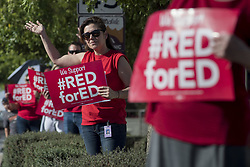 April 25, 2018 - Scottsdale, Arizona, U.S - Scottsdale, Arizona teacher, Alicia Majercin, reacts to motorists honking in support and colleagues demonstrate for improved funding for all Arizona schools.  Teachers are planning a walk-out statewide on Thursday, April 26 if Governor Doug Ducey and the Legislature fail to make changes to the next state budget to overcome at least ten years of budget shortcomings for teachers, equipment and facilities. Arizona is ranked 49th in the nations for benchmark statistics in measuring the quality of schools. (Credit Image: ©  via ZUMA Wire)