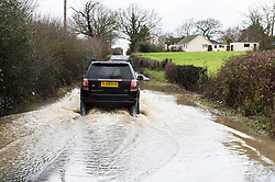 © Licensed to London News Pictures. 24/12/2013. Billericay, UK. UK Weather. After a night of torrential rain and wind many roads became flooded across the south of England. Some drivers took the advice of the AA and did not risk driving through the water. Others carried on and continued their journey on the last day of shopping before Christmas.Photo credit : Simon Ford/LNP