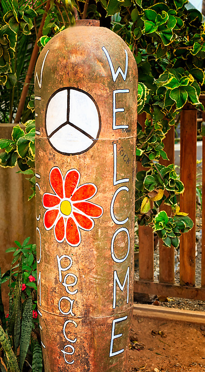 Peace Bomb: An unexploded bomb, a remnant of the American bombing attack during the Vietnam War, has been decorated with flowers and peace signs and sits outside of a local bar in Nong Khiaw Laos.