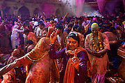 People drenched in colors celebrating the event of braj holi in the Radha Rani Complex in Barsana, Uttar Pradesh, India.