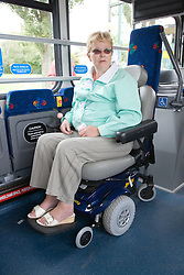 Woman sitting on bus in designated area for wheelchair users