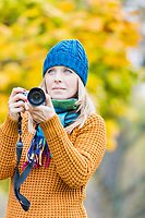Portrait of beautiful woman photographing lovely maple trees in park