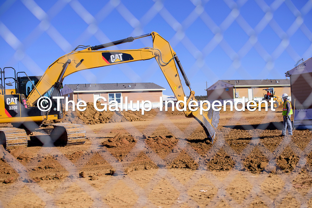 Construction workers stand by as an excavator readies a build site at the Navajo Housing Authority site near Ramah Tuesday.