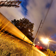 Train motion at railroad crossing at night along First Street along the Missouri River in Kansas City, Missouri.