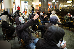 © Licensed to London News Pictures . 05/11/2015 . Manchester , UK . Protesters wearing Guy Fawkes masks at an Anonymous demonstration outside a branch of Starbucks in the Arndale Centre in Manchester , UK , this evening (5th November 2015) . Photo credit : Joel Goodman/LNP