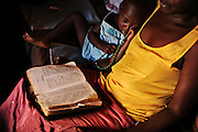 12-03-20   -- KAMPALA, UGANDA --  Immanuel Otim, 3, rests as Lilliann Okelo reads the Bible in her home in the Acholi Quarter on March 20.  Photo by Daniel Hayduk