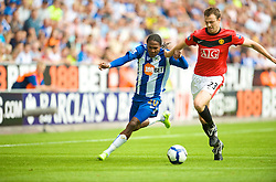WIGAN, ENGLAND - Saturday, August 22, 2009: Manchester United's Jonny Evans and Wigan Athletic's Hugo Rodallega during the Premiership match at the DW Stadium. (Photo by David Rawcliffe/Propaganda)