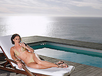 Woman lying on deck chair sipping champagne at poolside by ocean