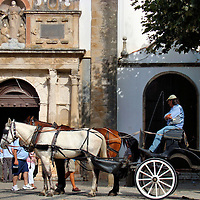 Carriage Outside Church of Santa Maria in Óbidos, Portugal <br /> The streets of Óbidos, Portugal, are mostly cobblestone so it's best to see this Medieval town by foot or, when you get tired, go for a horse carriage ride.  This driver is waiting outside the Church of Santa Maria which is the site where the arranged marriage of King Afonso V to Princess Isabella of Coimbra was celebrated in 1441. What made this event significant is that they were cousins and he was ten and she was only eight years old.