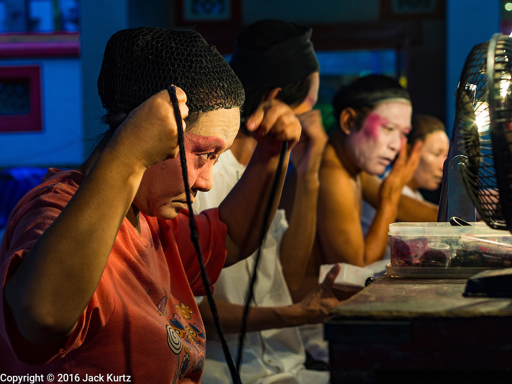 """30 JUNE 2016 - BANGKOK, THAILAND: Performers put on their makeup before a Chinese opera performance at Chiao Eng Piao Shrine in Bangkok. Chinese opera was once very popular in Thailand, where it is called """"Ngiew."""" It is usually performed in the Teochew language. Millions of Chinese emigrated to Thailand (then Siam) in the 18th and 19th centuries and brought their culture with them. Recently the popularity of ngiew has faded as people turn to performances of opera on DVD or movies. There are about 30 Chinese opera troupes left in Bangkok and its environs. They are especially busy during Chinese New Year and Chinese holidays when they travel from Chinese temple to Chinese temple performing on stages they put up in streets near the temple, sometimes sleeping on hammocks they sling under their stage.       PHOTO BY JACK KURTZ"""