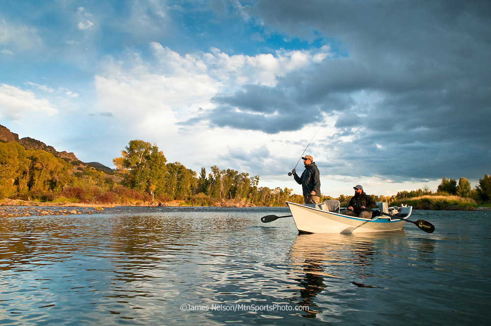 Jim Hinman fly fishes from the front of a drift boat as Matt Kelley rows down the South Fork of the Snake River, Idaho.
