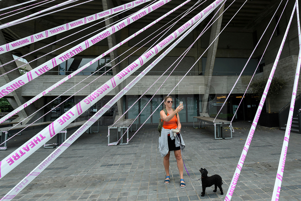© Licensed to London News Pictures. 03/07/2020. LONDON, UK. A woman takes selfie amongst the pink tape wrapped around the National Theatre on the South Bank as part of the #MissingLiveTheatre initiative, a project by theatre designers Scene Change to support those in the live theatre industry through Covid-19 and to help theatres bring shows back into production.  So far, 50 theatres across the UK have signed up to the initiative.  Theatres are remain closed even though the UK government has relaxed certain coronavirus pandemic lockdown restrictions allowing other businesses to reopen.  Photo credit: Stephen Chung/LNP