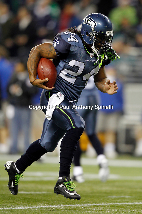 Seattle Seahawks running back Marshawn Lynch (24) runs the ball during pregame warmups with his green gloves attached to his face-mask at the NFL week 13 football game against the Philadelphia Eagles on Thursday, December 1, 2011 in Seattle, Washington. The Seahawks won the game 31-14. ©Paul Anthony Spinelli