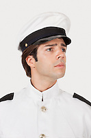 Young navy officer looking away against gray background