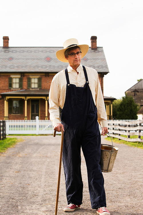 Mo Rocca stands in front of Firestone Farm at Greenfield Village dressed up as an early American farmer for a story for The Henry Ford's Innovation Nation.  Photographed for The Henry Ford by set photographer Kristina Sikora
