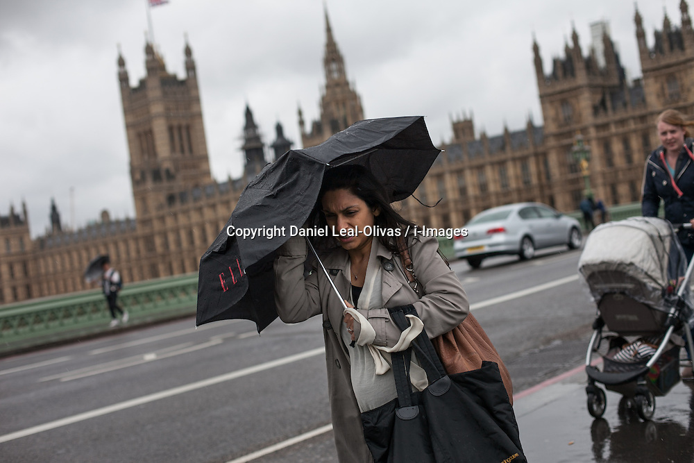 A pedestrian covers herself with an umbrella amid rain and wind, at Westminster Bridge, London, UK, 14th May, 2013. Photo by: Daniel Leal-Olivas / i-Images