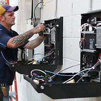 Paul Landry, an installer with City Tele Coin in Bossier City, Louisiana, installs two monitor systems he inside the A Pod cell at the Lee County Jail on Tuesday.